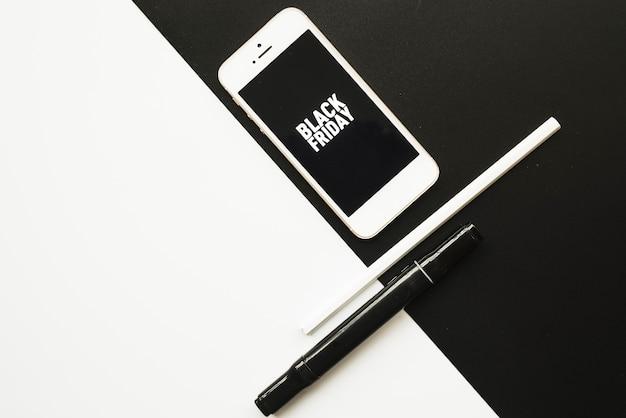 Smartphone com inscrição de sexta-feira negra na mesa branca preta