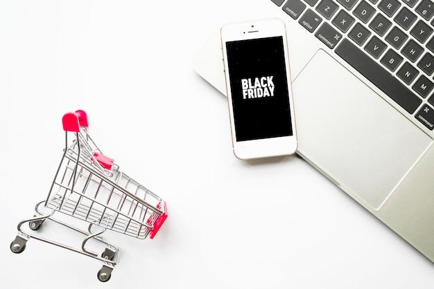Smartphone com inscrição de sexta-feira negra na mesa de luz