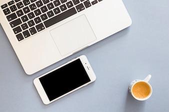 Smartphone com laptop e xícara de café
