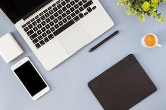 Smartphone com laptop, xícara de café e notebook