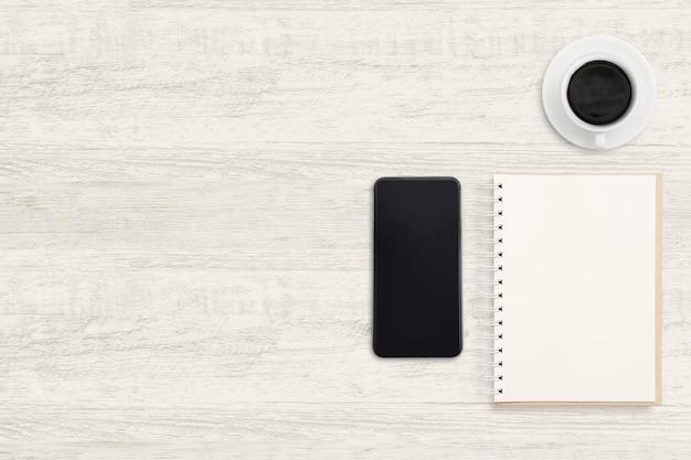 Smartphone com notebook e uma xícara de café na madeira.