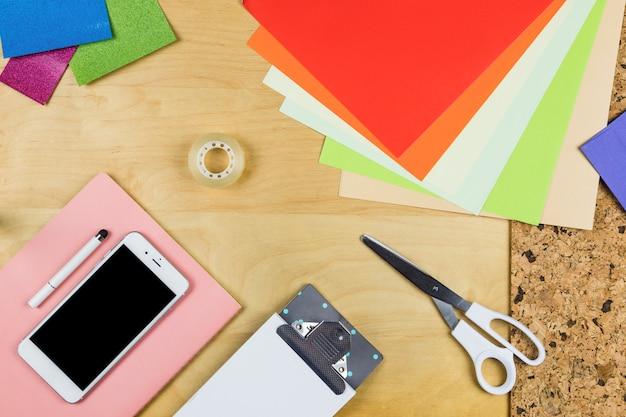 Smartphone com papéis brilhantes na mesa