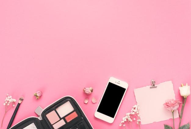 Smartphone com papel em branco, rosas e cosméticos