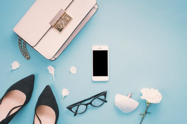 Smartphone com sapatos de mulher e flor na mesa