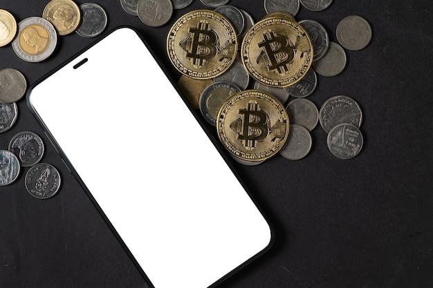 Smartphone com tela branca e bitcoin na mesa de pedra preta, dinheiro virtual eletrônico e pagamento em rede internacional