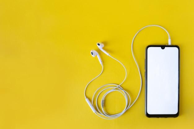 Smartphone com tela branca em branco se conecta a fones de ouvido na vista superior amarela. fone de ouvido conectado ao celular.