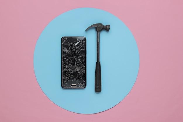 Smartphone com tela de vidro quebrado e martelo em fundo rosa azul