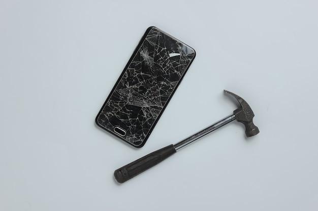 Smartphone com tela de vidro quebrado e martelo em um fundo branco