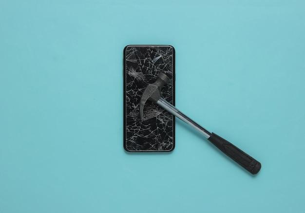 Smartphone com tela de vidro quebrado e martelo