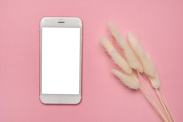 Smartphone com tela em branco e flores secas na superfície rosa
