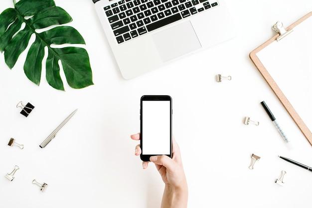 Smartphone com tela em branco em mãos femininas