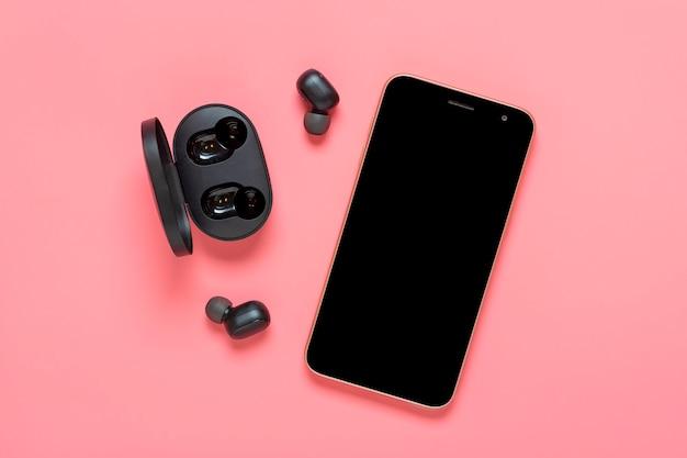 Smartphone com tela preta e fones de ouvido sem fio, cápsula do carregador em fundo rosa simulação