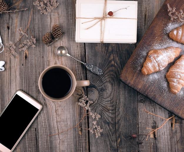 Smartphone com tela preta em branco, copo cerâmico marrom com café e croissants cozidos polvilhados com açúcar de confeiteiro