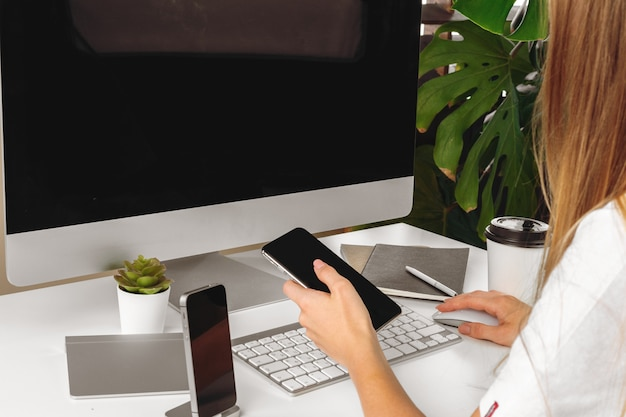 Smartphone com tela preta nas mãos femininas. computador, teclado e material de escritório em um