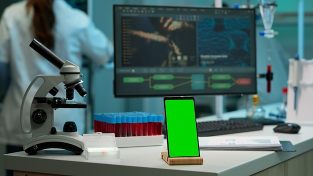 Smartphone com tela verde trabalhando em laboratório com mock up, display de chroma key, enquanto engenheiro profissional testa a evolução do vírus em segundo plano. laboratório de desenvolvimento de alta tecnologia com amostras de sangue