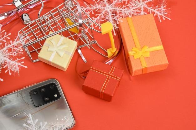 Smartphone com três câmeras e decoração de natal em fundo vermelho
