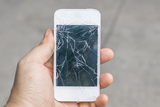 Smartphone com uma tela rachada, mão que guarda o telefone celular quebrado, conceito da tecnologia.