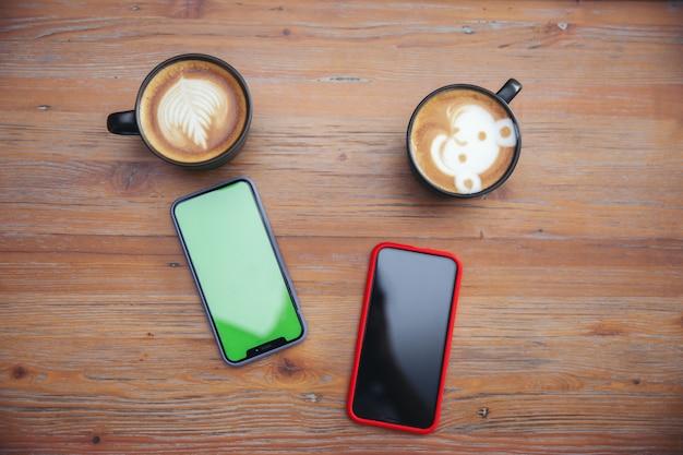 Smartphone com uma xícara de café na mesa de madeira no café café.