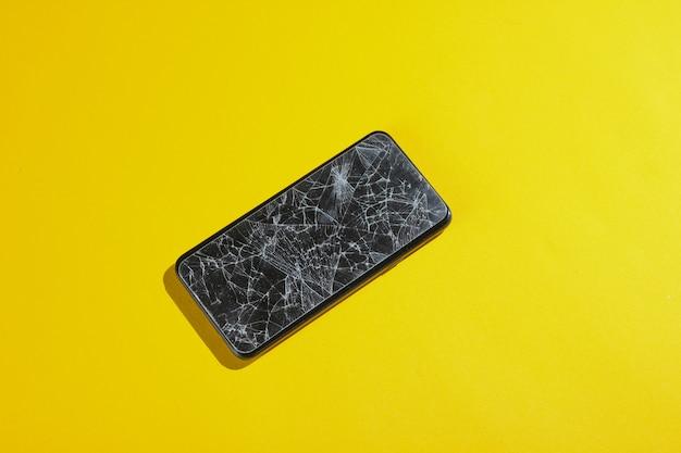 Smartphone com vidro protetor quebrado na mesa amarela.