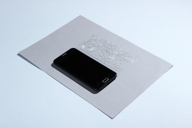 Smartphone com vidro protetor quebrado na mesa de papel. vista lateral