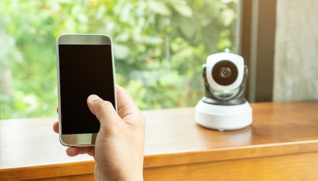 Smartphone, conectando-se com a câmera ip de segurança em uma mesa de madeira.