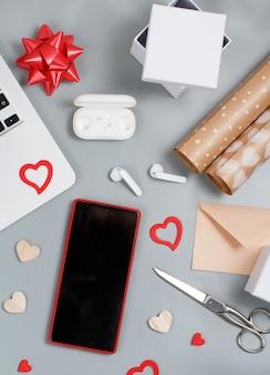 Smartphone, corações, laptop, fones de ouvido, tesouras, caixas de presente e vista superior do papel de embrulho. conceito de dia dos namorados