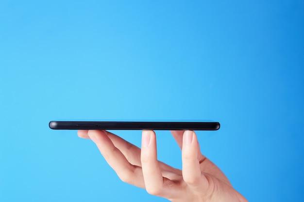 Smartphone da posse da mão no fundo azul. layout para designe