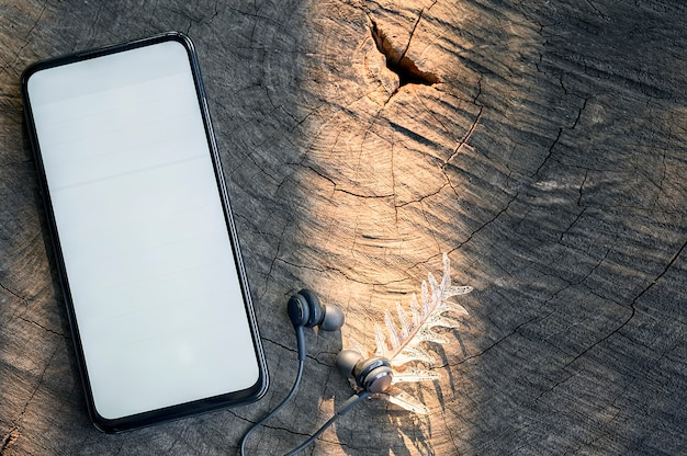 Smartphone de maquete com tela em branco branca e fone de ouvido no fundo de madeira.