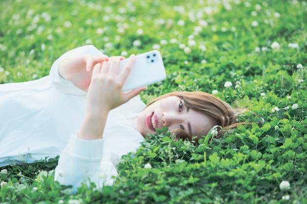 Smartphone de operação da jovem mulher asiática
