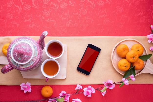 Smartphone de tela em branco com bule e xícara de chá, fruta laranja na toalha de mesa vermelha