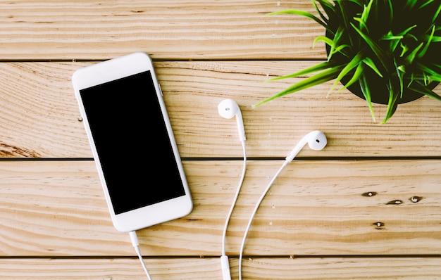 Smartphone de tela em branco com fone de ouvido na mesa de madeira