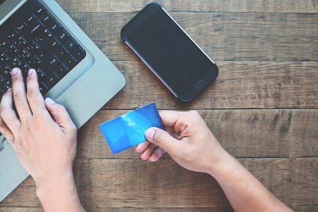 Smartphone de tela em branco para aplicação de simulação com homem usando cartão de crédito e computador portátil