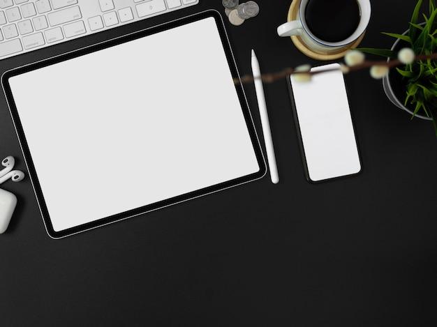 Smartphone de tela em branco, tablet, outros suprimentos, decorações e espaço de cópia na mesa de trabalho moderna escura