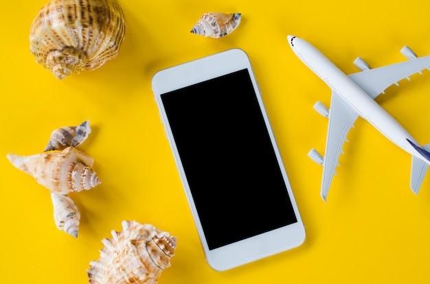 Smartphone de tela vazia, avião decorativo e conchas, modelo para apresentação do aplicativo.