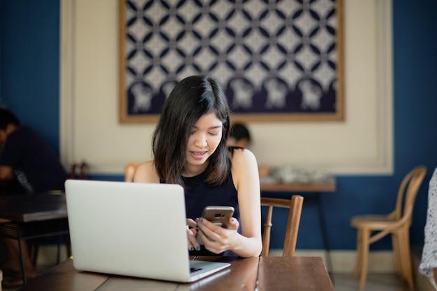 Smartphone de utilização autônomo da menina asiática ao trabalhar com seu portátil no coffeeshop.