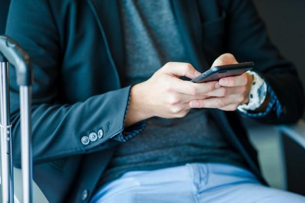 Smartphone do close up nas mãos masculinas para dentro no aeroporto.