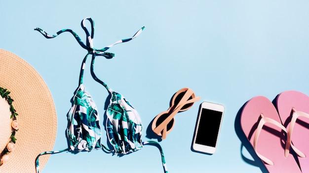 Smartphone e acessórios à beira-mar na luz de fundo