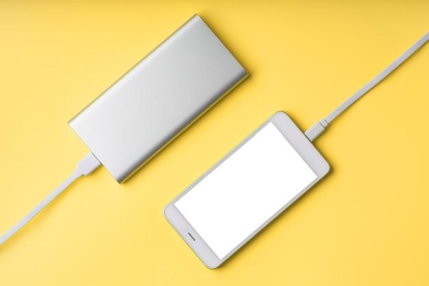 Smartphone e banco de energia em uma superfície amarela isolada