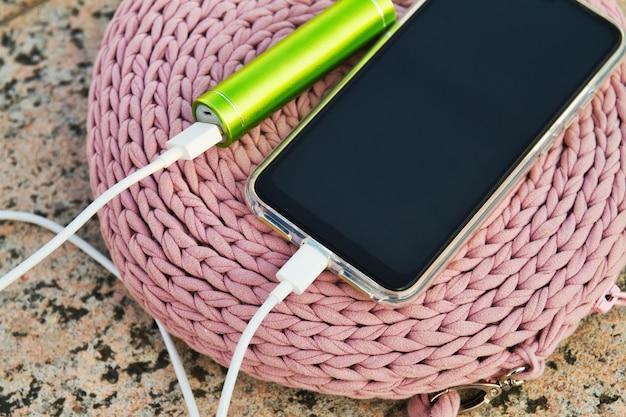Smartphone e banco de energia externa estão em uma bolsa de malha para mulher no parque durante o carregamento
