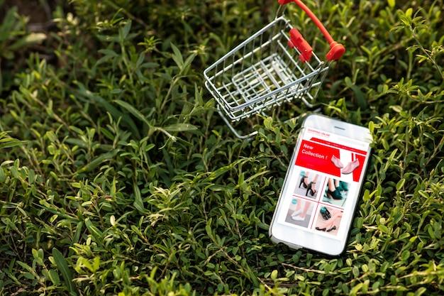 Smartphone e carrinho de compras na grama verde. compras on-line ou conceito de comércio eletrônico no site para ambientalmente.