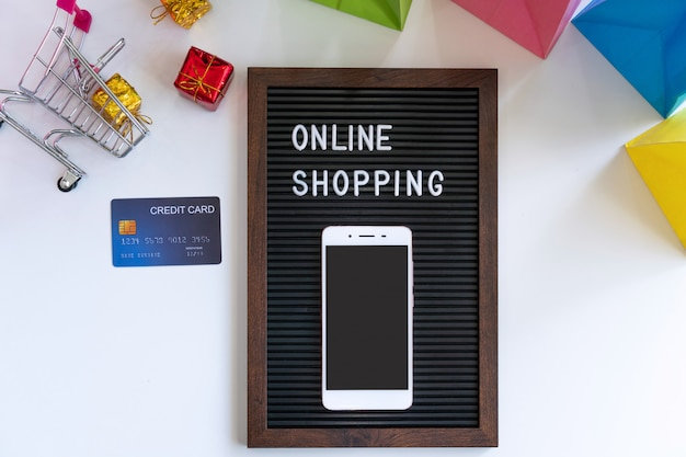 Smartphone e cartão de crédito na mesa de compras on-line e novo conceito normal