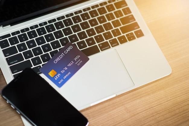 Smartphone e cartão de crédito no laptop