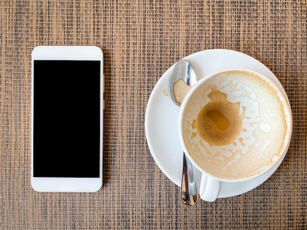 Smartphone e copo de café vazio na mesa de madeira na vista superior
