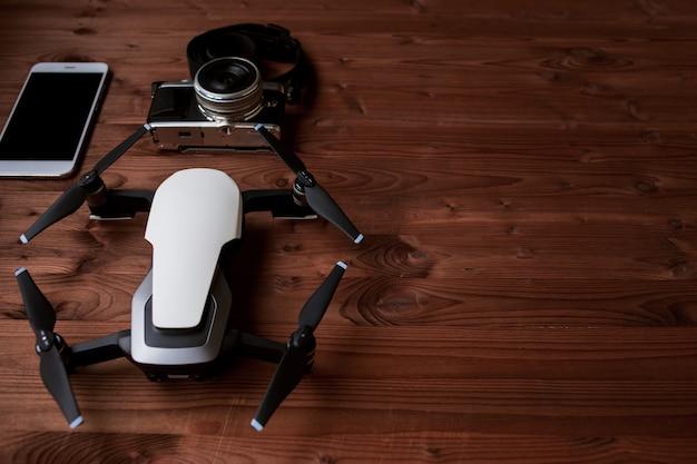 Smartphone e drone em fundo de madeira