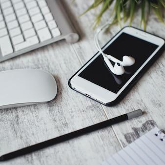 Smartphone e fone de ouvido com teclado de mouse na mesa de madeira