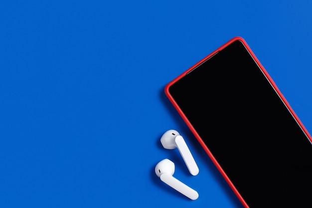 Smartphone e fones de ouvido sem fio brancos com a vista superior da capa em fundo azul