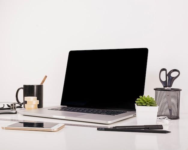 Smartphone e laptop com tela preta em branco na mesa de escritório