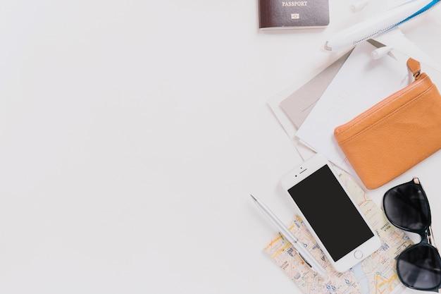 Smartphone e óculos de sol perto de bolsa e mapas