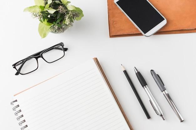 Smartphone e óculos perto de papelaria e planta