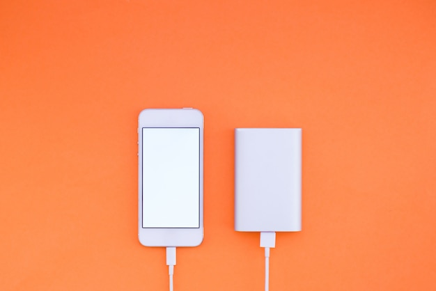 Smartphone e powerbank em fundo laranja. o powerbank carrega o telefone contra a parede. configuração plana